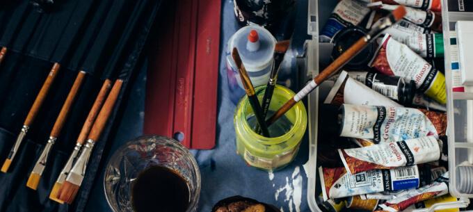 artist tools brushes paints green jar