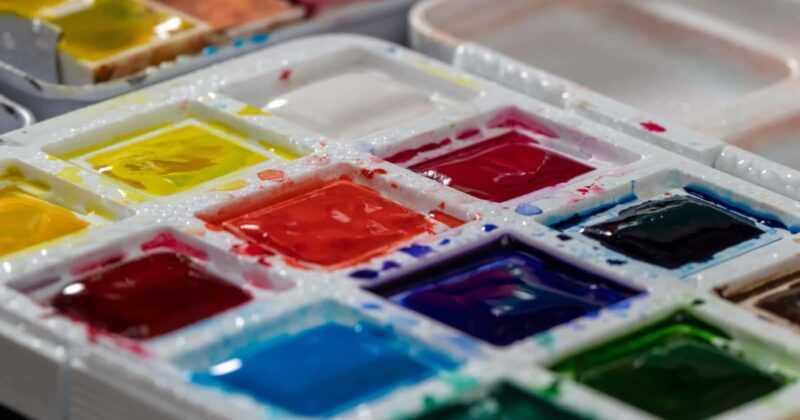 several watercolor palettes with yellows, reds, blues, greens